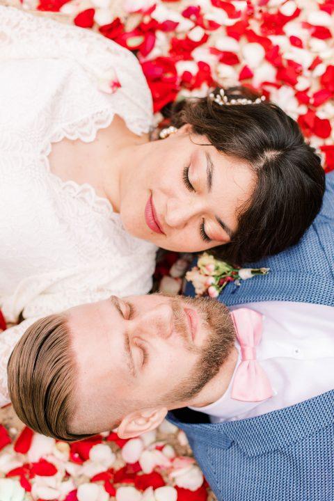 Braut und Bräutigam liegen auf einem Meer aus Rosenblättern
