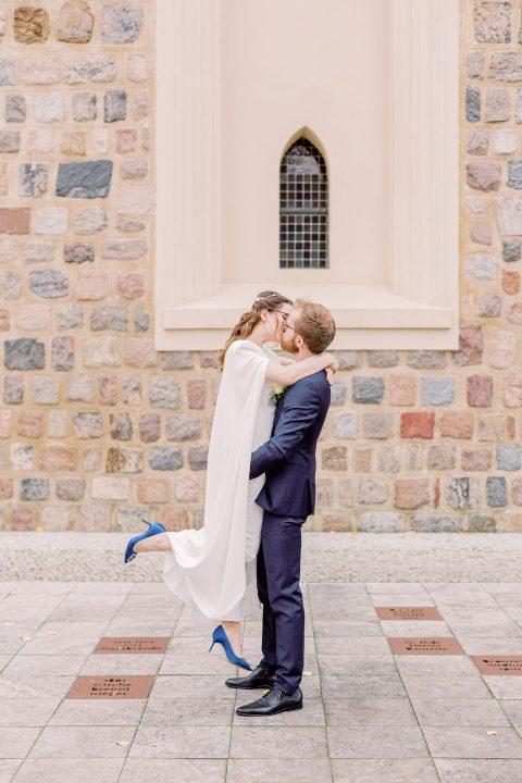 Brautpaar vor einer Kirche, küsst sich innig