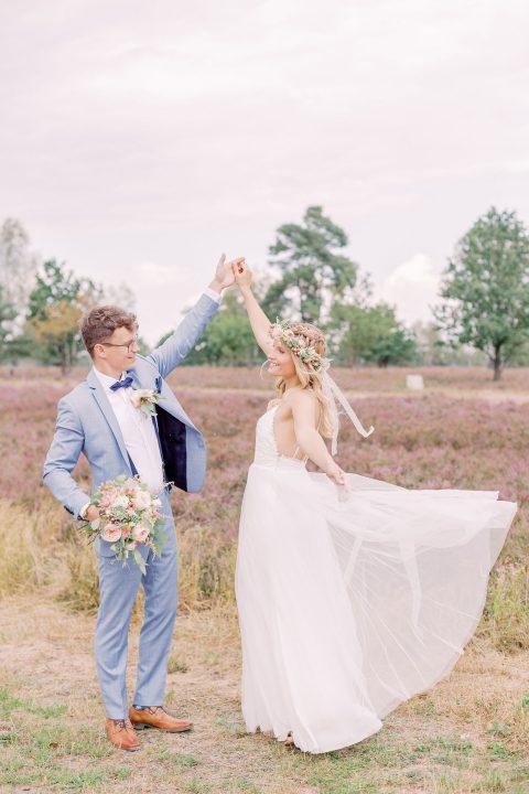 Brautpaar tanzt in der Lüneburger Heide im Wind