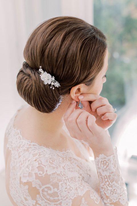 Braut steckt sich Ohrring an