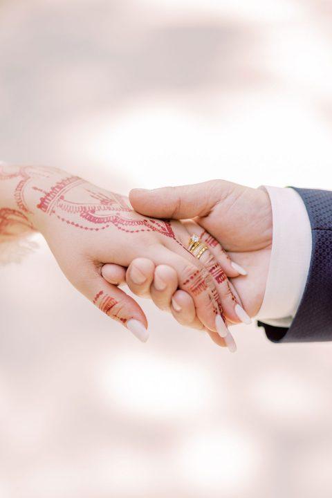 Hand einer Braut mit Henna, welche vom Bräutigam geführt wird